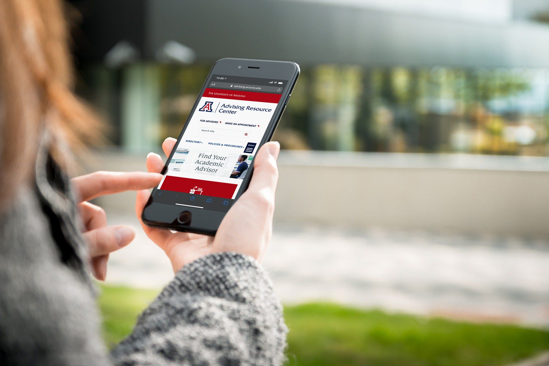 Woman holding phone which displays the Advising Resource Center website's home page
